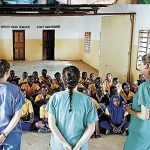 The Trinity students giving an oral health presentation to local school children