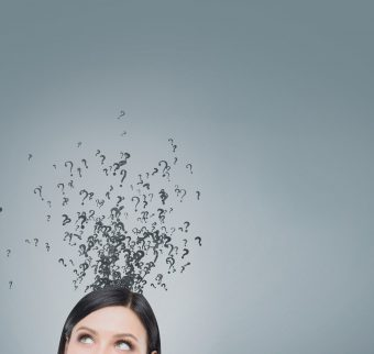 Top of a woman's head with question marks floating above it